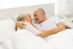 Happy senior coupler lying in bad at home Stock Images