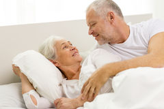 Happy senior coupler lying in bad at home Royalty Free Stock Photos