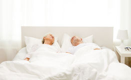 Happy senior coupler lying in bad at home Royalty Free Stock Images