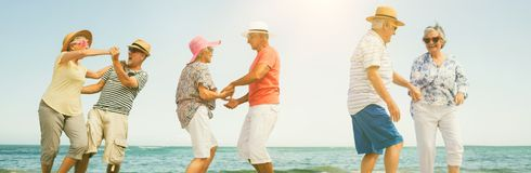 Happy senior couples dancing. On shore at beach royalty free stock images