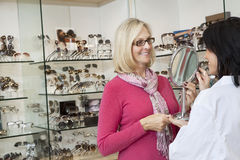 Happy senior customer looking into mirror in store Royalty Free Stock Images