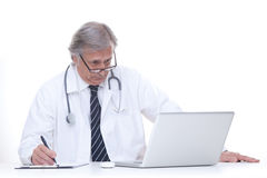 Happy senior doctor with stethoscope working with laptop isolated on white Royalty Free Stock Images