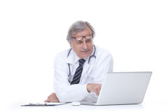 Happy senior doctor with stethoscope working with laptop isolated on white Royalty Free Stock Image