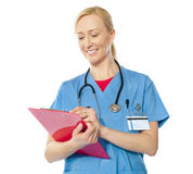 Happy senior doctor writing on clipboard Stock Image