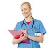 Happy senior doctor writing on clipboard Stock Image