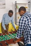 Happy senior father and adult son playing table football. At home royalty free stock photography