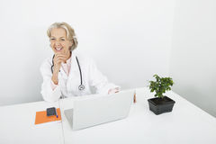 Happy senior female doctor with laptop at desk in clinic Royalty Free Stock Images