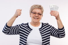 Happy senior female holding currencies dollar and clenching her fist, concept of financial security in old age Stock Image