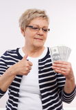 Happy senior female holding currencies dollar and showing thumbs up, concept of financial security in old age Royalty Free Stock Photography
