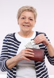 Happy senior female holding wallet with currencies dollar, concept of financial security in old age Stock Image