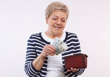 Happy senior female holding wallet with polish currency money, concept of financial security in old age Royalty Free Stock Photo