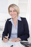 Happy senior female manager - portrait in the office. Royalty Free Stock Photo