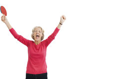 Happy senior female table tennis player with arms raised celebrating victory Stock Image