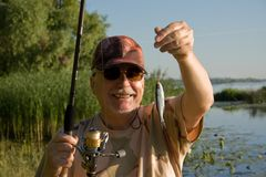 Happy senior fisherman. Royalty Free Stock Image