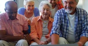 Happy senior friends having fun while using laptop 4k stock video footage