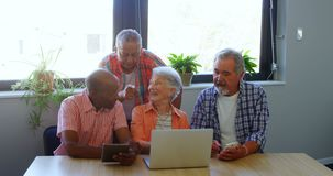 Happy senior friends interacting with each other while using laptop 4k stock video footage