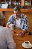 Senior friends playing jenga game on table in bar. Happy senior friends playing jenga game on table in bar Stock Photo