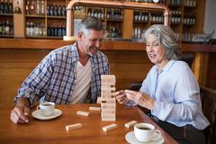 Senior friends playing jenga game on table in bar. Happy senior friends playing jenga game on table in bar Royalty Free Stock Photos