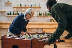 Table football. Happy senior friends playing table football at bar Stock Photography