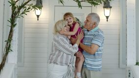 Happy senior grandfather and grandmother couple holding granddaughter in hands in porch at home
