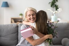 Happy senior grandma hugging granddaughter thanking for gift and. Happy senior grandma hugging granddaughter thanking for present holding flower bouquet, smiling stock photo