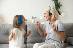 Happy grandmother and granddaughter listening to music in headph. Happy senior grandmother and little kid granddaughter laughing listening to music in earphones stock images