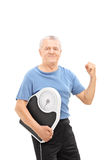 Happy senior with gripped fist holding a weight scale Stock Photo