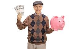 Happy senior holding bundles of money and a piggybank. Isolated on white background Stock Photography