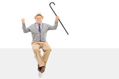 Happy senior holding a cane seated on a panel Royalty Free Stock Photo