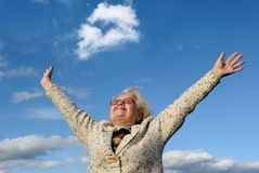 Happy senior lady. Image of an excited old woman with her arms raised up in the air as she smiled to the sky in pride Stock Photos