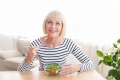 Happy senior lady eating fresh salad at home stock images