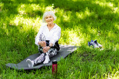 Happy senior lady having rest time after exercise outdoors Royalty Free Stock Images