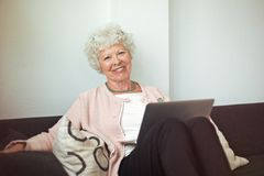 Happy Senior Lady at Home with Laptop Royalty Free Stock Photo