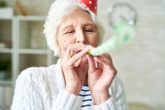 Happy Senior Lady at Party. Head and shoulders portrait of happy senior woman blowing party horn and wearing birthday cap while enjoying holiday celebration at stock photography