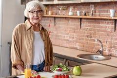 Happy senior lady preparing breakfast stock photography
