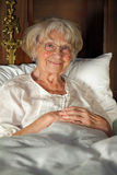 Happy senior lady relaxing in bed Royalty Free Stock Photo