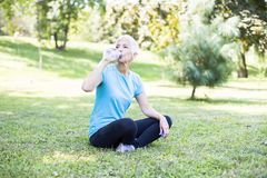 Happy senior lady relaxing after training in park royalty free stock photography
