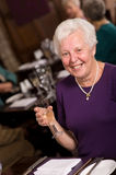 Happy senior lady in restaurant Stock Photo