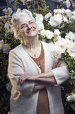 Happy senior lady in the rose garden Stock Photos
