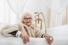Happy senior lady sitting in bath Stock Photo