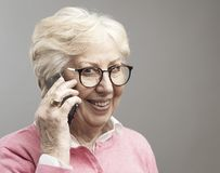 Happy senior lady talking on the phone. Modern happy senior lady having a phone call on her smartphone and smiling, elderly and communication concept stock photography