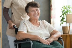 Happy senior lady after treatment. Close-up photo of happy senior lady in a wheelchair feeling better after successful treatment Royalty Free Stock Images