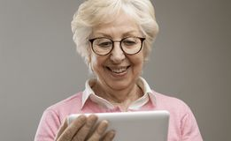 Happy senior lady using a digital tablet. Happy senior lady using a digital touch screen tablet, she is connecting online and social networking stock photos
