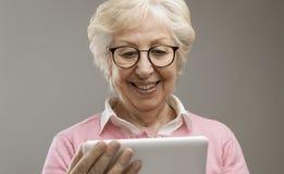 Happy senior lady using a digital tablet stock photos