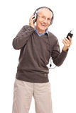 Happy senior listening to music on headphones Stock Images