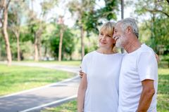 Happy senior loving couple relaxing at park embracing together in morning time. old people  hugging and enjoying spending time in stock images