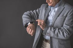 Happy senior male checking time on arm. Smiling old businessman pointing at modern watch locating on hand. Accessory concept. Copy space Royalty Free Stock Image