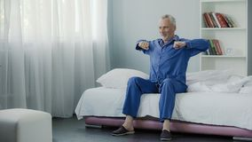 Happy senior male doing morning gymnastics in his bed, good mood, optimistic. Stock footage Royalty Free Stock Photos