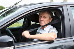 Happy senior male fastens safety belt sitting in car Royalty Free Stock Photography