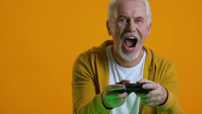 Happy senior male playing video game console, retirement hobby, entertainment. Stock footage stock video